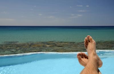 man-tanning-by-ocean